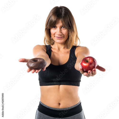 Sport Woman Holding An Apple In One Hand And Donut In Other Hand