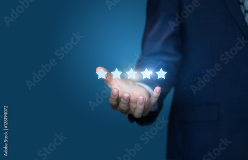 Fotografía  Businessman hand holding five stars isolated on blue background