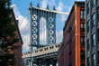 The Manhattan Bridge and a Brooklyn street sidelined by old red brick buildings