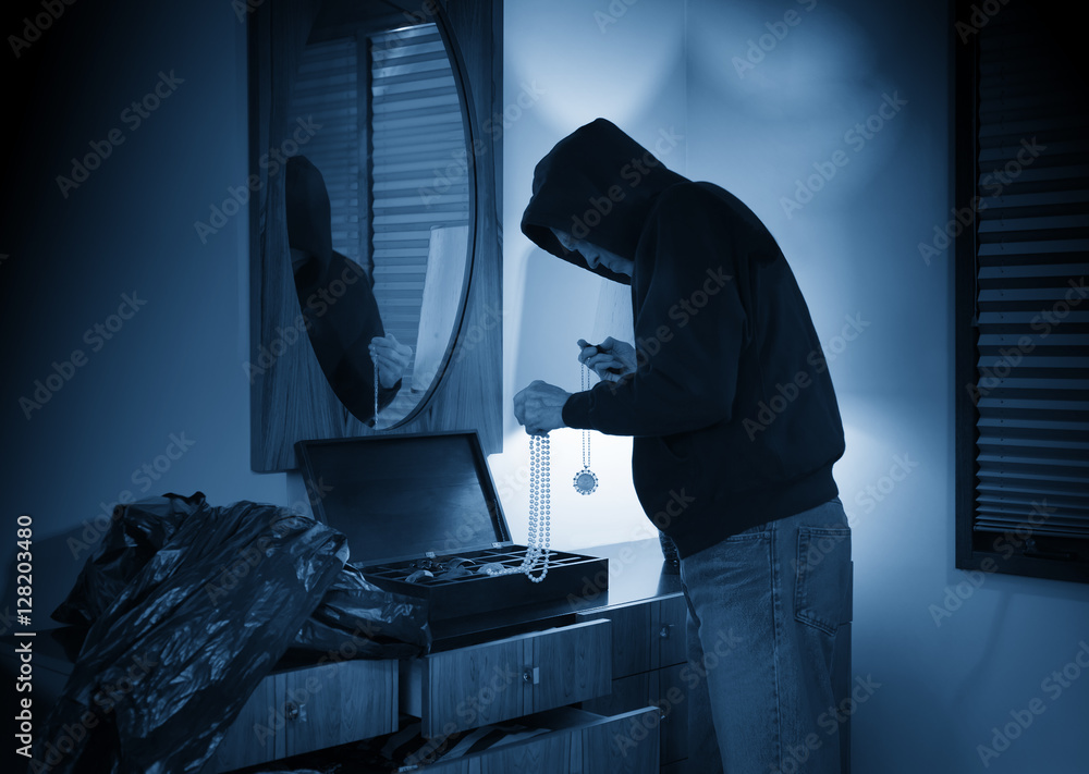 Fototapeta Hooded burglar ransacking a jewelry box in a home