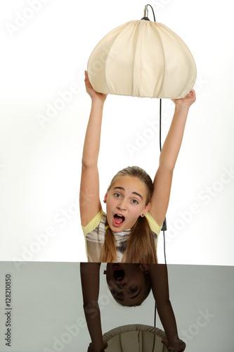 Foto  Śliczna dziewczynka z lampą nad głowie, na białym tle.