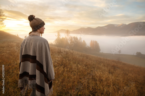 Fotografie, Obraz  young woman hiking at mountain peak above clouds and fog Hiker girl wrapping in warm poncho outdoor