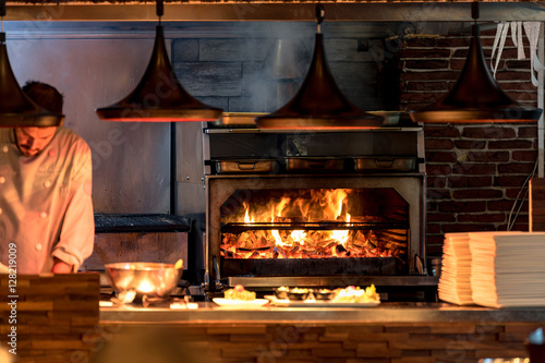 Burning grill in the oven at restaurant kitchen