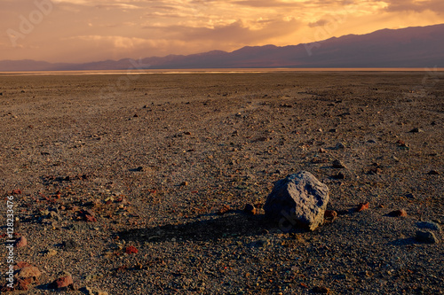Fotografie, Obraz  A lone boulder lies in an expansive, empty desert at sunset