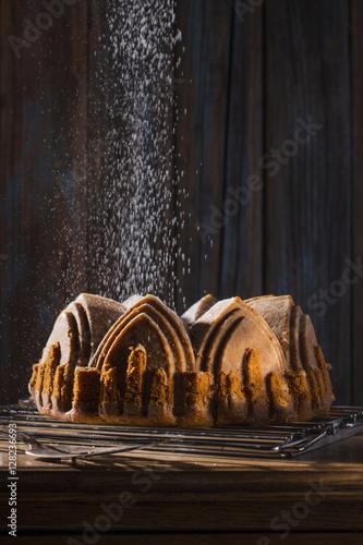 Fotografie, Obraz  Sprinkling Powdered Sugar over Apple Spice Cake