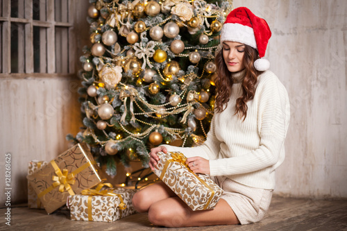 Obraz na plátně young pretty brunette woman unpacking gift box sitting near Christmas tree