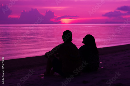 Aluminium Prints Pink Silhouette of the couple enjoying the sunset on the beach