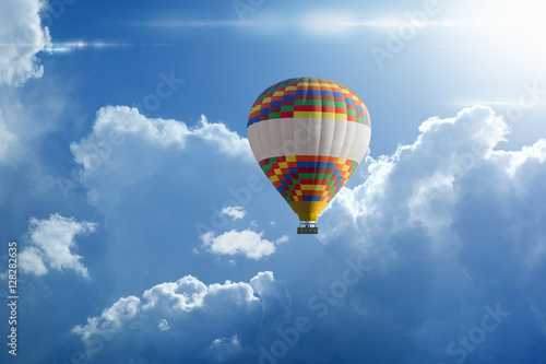 Hot air balloon rises very high in blue sky above white clouds Poster Mural XXL