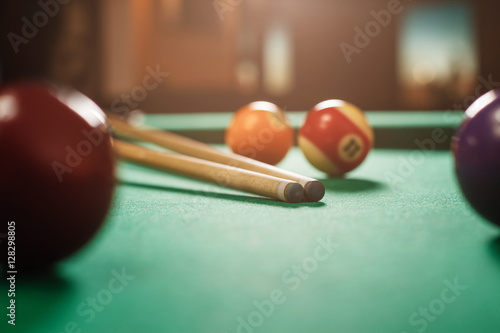 Canvas Print Two cues and spheres on a billiard table.