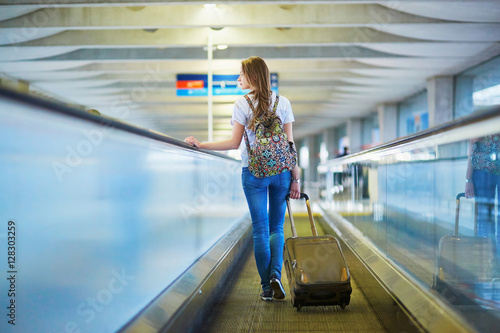 Fotografie, Obraz  Beautiful young tourist girl with backpack and carry on luggage in international