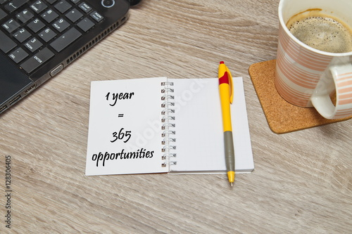 """Fényképezés  Open notebook with Text """"One year 365 opportunities"""" and a cup of coffee on wooden background"""