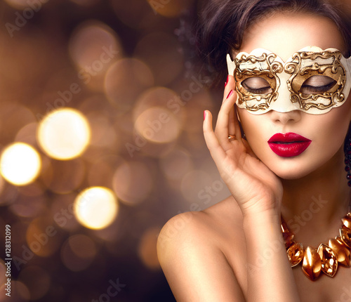 Beauty model woman wearing venetian masquerade carnival mask at party. Christmas and New Year celebration