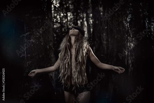 Fotografie, Obraz  Young beautiful blindfolded woman in forest. Alone in the dark