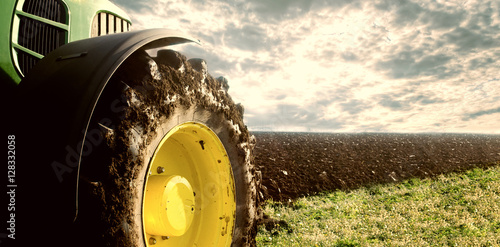 Agriculture. Tractor plowing field, Wheels covered in mud, field in the background. Cultivated field. Agronomy, farming, husbandry concept.