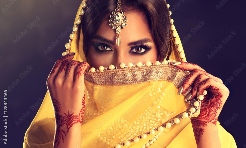 Fototapety, obrazy: Beautiful indian girl . Young hindu woman model  with tatoo mehndi  and kundan jewelry . Traditional Indian costume yellow saree . Indian or Muslim woman covers her face.