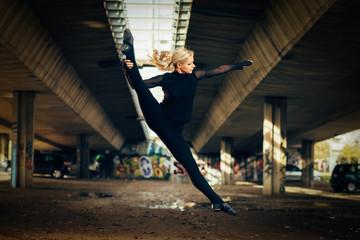 Attractive jazz ballerina dancing under the overpass