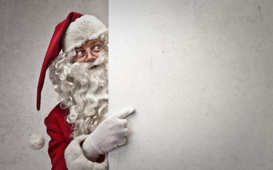 Santa Claus indicating a white cardboard