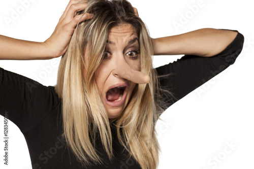 Fototapeta shocked young woman looking in her elongated nose
