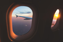 Sunset Aerial View Through Airplane Window Over Wings