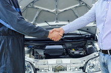 Car Service. Mechanic And Customer Shaking Hands. Excellent Cooperation Between Car Mechanic And Customer.