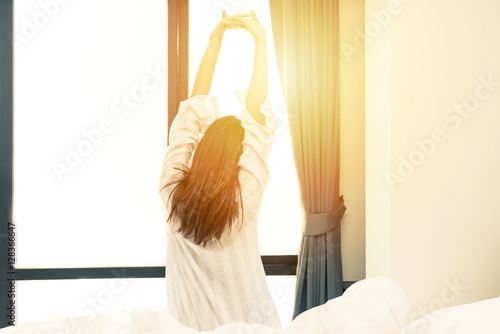 Fotografie, Obraz  Rear view of woman stretching in bed after wake up in morning with sunlight