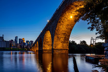 A View Of The Beautiful Stone Arch Bridge Of Minneapolis, MN, USA At Dusk, Showing Part Of The City Skyline