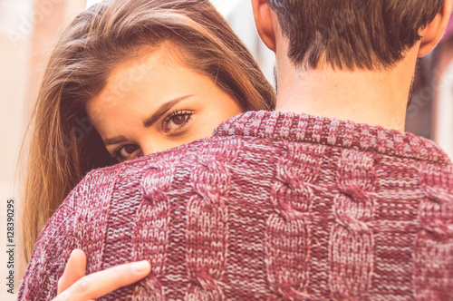 Valokuva  Attractive girl hugging her boyfriend and looking at the camera