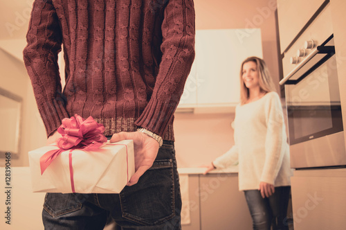 Fotografering  Man is hiding behind his back a gift for his girlfriend