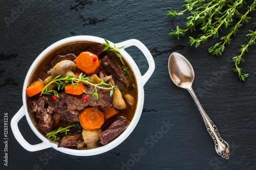 Fotografie, Obraz  Beef Bourguignon in a white soup bowl on black stone background, top view