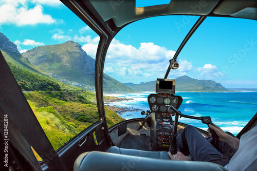 Tuinposter Helicopter Helicopter cockpit flies in Misty Cliffs, Cape Peninsula in South Africa, with pilot arm and control board inside the cabin.