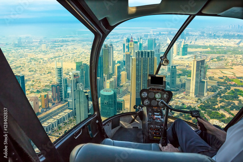Foto op Plexiglas Helicopter Helicopter cockpit flies in skyscrapers of Dubai downtown skyline on Sheikh Zayed Road, United Arab Emirates, with pilot arm and control board inside the cabin.