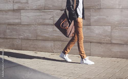 Fotografia  Fashion african man in black rock leather jacket with bag walkin