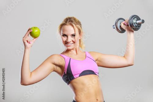 Fotografia  Diet fit body. Girl holds dumbbells and apple fruit