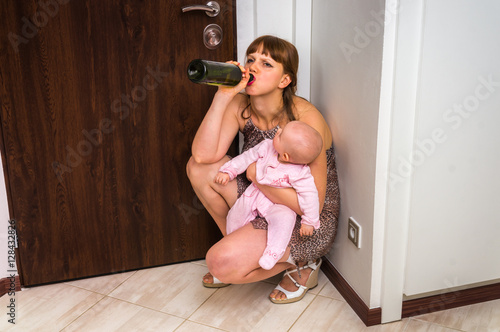 Fotografie, Obraz  Drunk reckless woman drinking alcohol and holding her baby