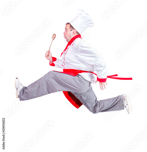 Photo  fat chef running with a wooden spoon on a white background