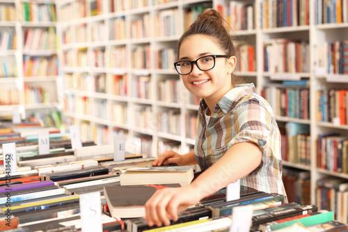 Fototapeta Dziewczynka w księgarni wybiera książkę obraz