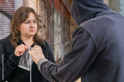 Photo  Young addicted woman is taking white pills from drug dealer.