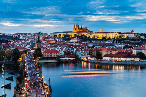 Pretty night time illuminations of Prague Castle, Charles Bridge and St Vitus Cathedral reflected in the Vltava river running through the heart of the city of Prague in the Czech Republic Poster