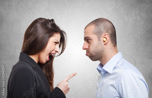 Fotografie, Obraz  Man using earplugs in his ears in front of an angry woman