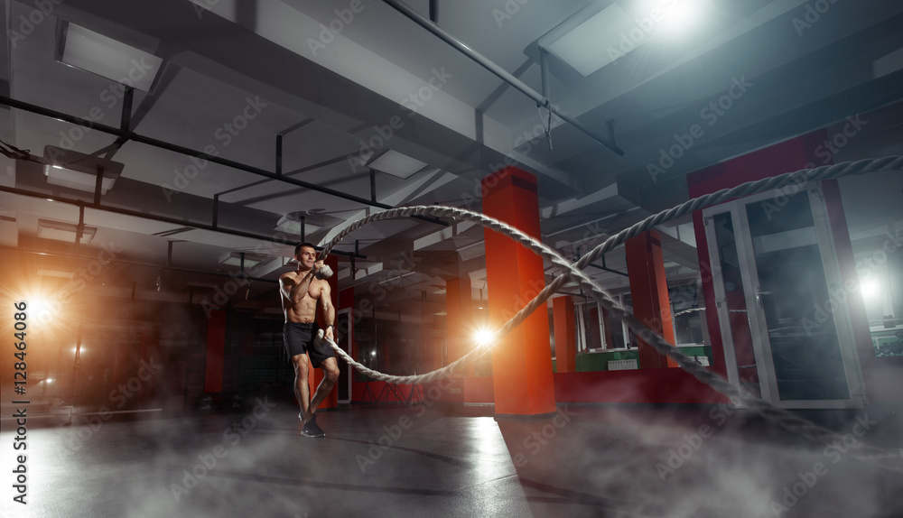 Fototapety, obrazy: Fitness man working out with battle ropes at a gym