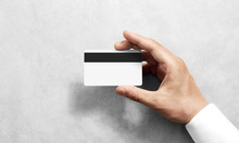 Hand Holding Blank White Credit Card Mockup With Black Magnetic Stripe, Back Side View. Plastic Bank-card Design Mock Up With Magstripe.