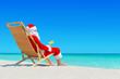 Christmas Santa Claus with fresh juice on sunlounger at tropical ocean beach