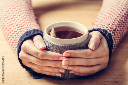 Cadres-photo bureau The Hot mug of tea warming woman's hands in retro jumper.