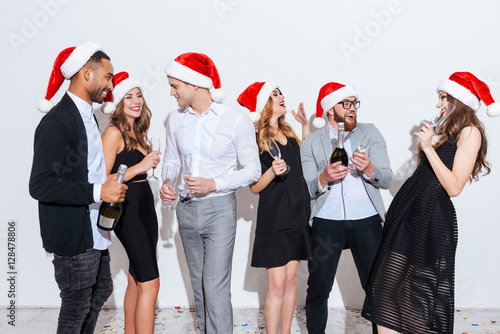 b1fac1a84 Happy people in santa claus hats drinking champagne and laughing ...