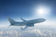 Airliner Flying Above The Clouds With The Sun In Blue Sky