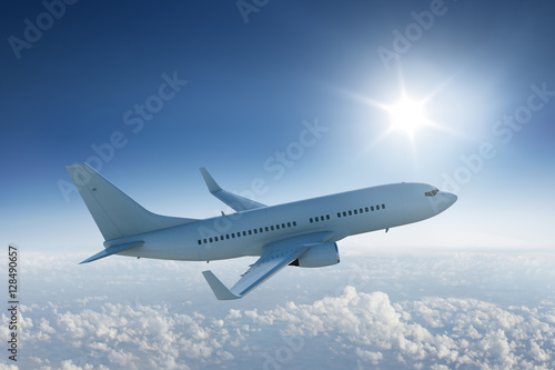 Fényképezés Airliner flying above the clouds with the sun in blue sky