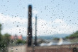 raindrops od window glass with industrial buildings and chimneys
