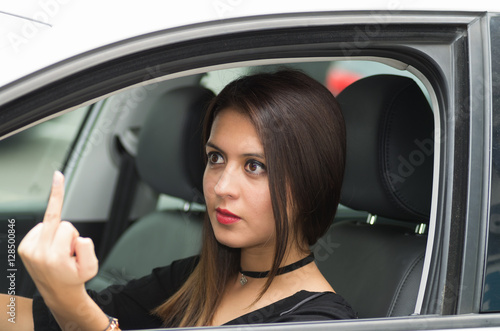 Fotografie, Obraz  Closeup young woman sitting in car giving the finger angrily, as seen from outsi