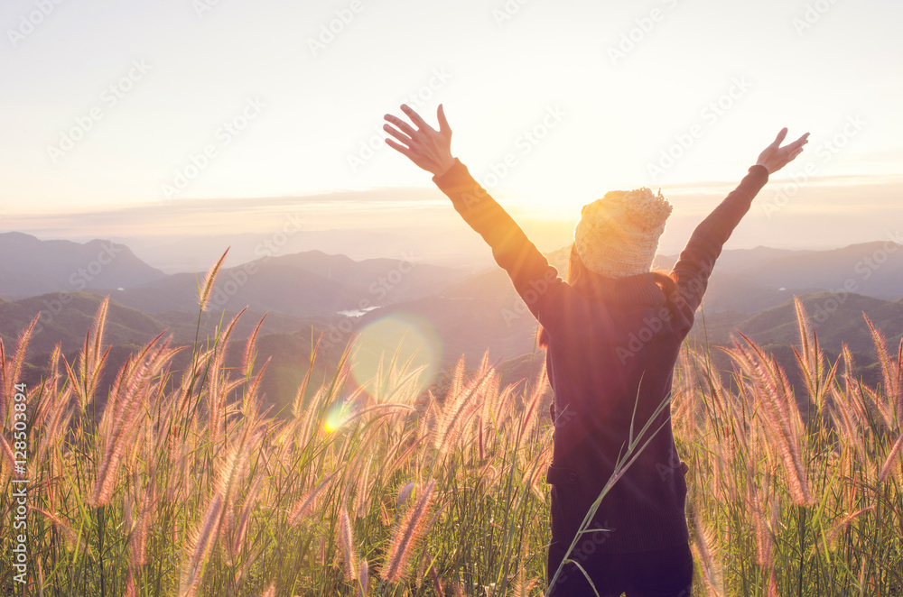 Fototapety, obrazy: Carefree Happy Woman Enjoying Nature on grass meadow on top of mountain cliff with sunrise. Beauty Girl Outdoor. Freedom concept. Len flare effect. Sunbeams. Enjoyment.