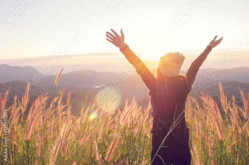 Carefree Happy Woman Enjoying Nature on grass meadow on top of mountain cliff with sunrise Fototapeta